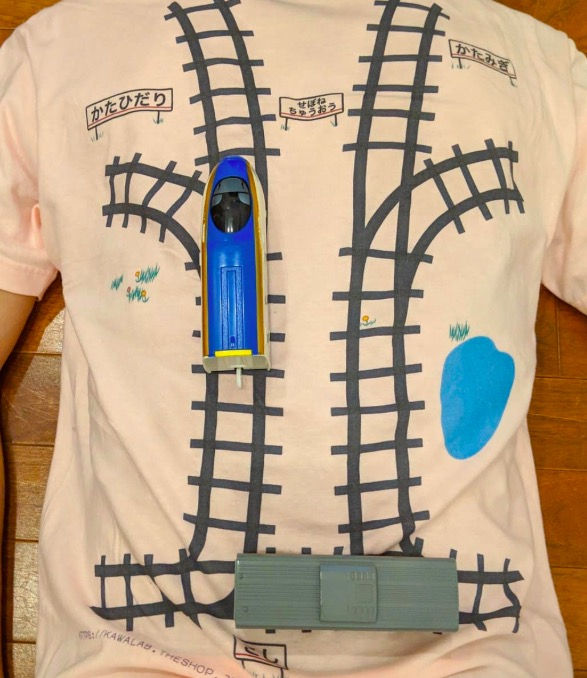 father designs a t-shirt with train track for son to do back massage