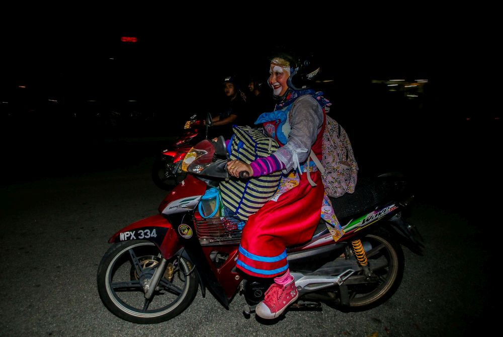 Nazirah on a bike for the stray animals dressed up as a clown on weekends